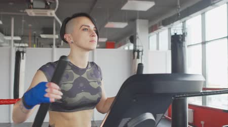 ação : Young short hair style woman running on a treadmill in a modern gym