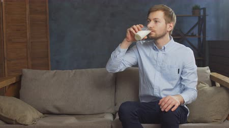 кальций : Man is drinking fresh glass of milk on the couch