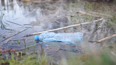 voluntário : Close up of man hand picking up plastic bottle from river, ecology and volunteering concept Stock Footage