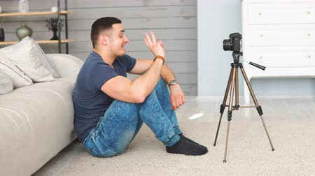 subscribers : Young man shooting video of himself using camera on tripod. modern technology and blogging freelance work concept