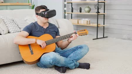 концентрация : Young man learning to play guitar using VR 360 headset while sitting on carpet at home