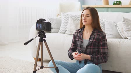 subscribers : Young girl blogger talking on digital camera recording video vlog at home