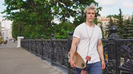 Young blonde man holding longboard deck in hands and walking on a summer day Стоковые видеозаписи
