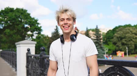 Portrait Of Young Blonde Man With Headphones Laughing Outdoor