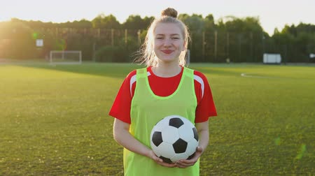 Portrait of a smiling female football player with a soccer ball at sunset