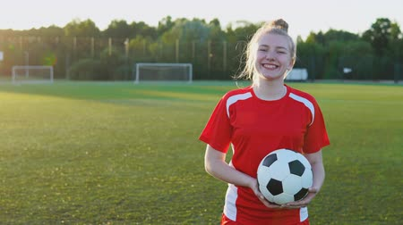Portrait of a smiling teen girl football player in red uniform with a soccer ball at sunset Стоковые видеозаписи