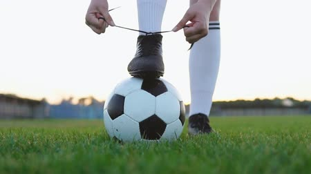Close up of a female soccer player tying shoelace on football field, slow motion