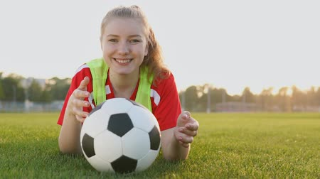 Portrait of a smiling teen girl football player lying on field with soccer ball in slow motion