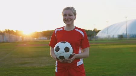 jarse : Portrait of teenage girl football player holding a soccer ball in hand and looking at camera