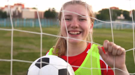 Portrait of a happy female high school soccer player with a soccer ball in slow motion