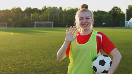 Portrait of smiling teenage girl football player with soccer ball waving hand and looking at camera