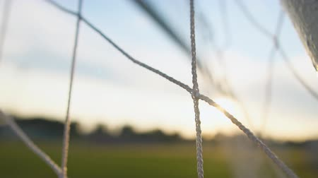 Close up of soccer or football net, view from behind the goal at sunset