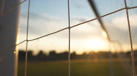 Macro of soccer or football net, view from behind the goal at sunset