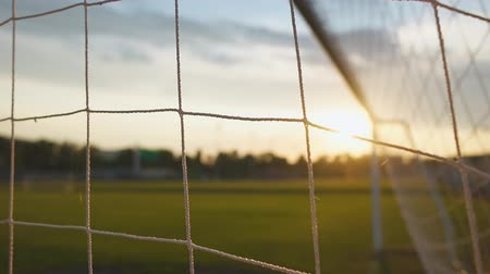 Close up of football goal net at sunset in slow motion Стоковые видеозаписи