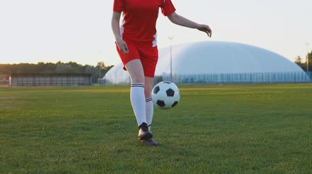 Female football player in red uniform kicking soccer ball at sunset in slow motion Стоковые видеозаписи