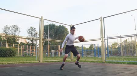 Young caucasian basketball player playing streetball in the street in slow motion