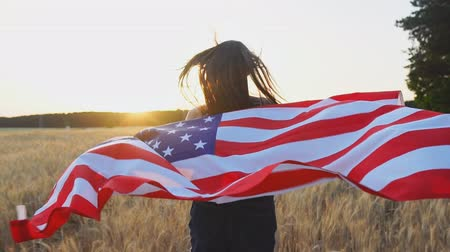 Young happy american girl running with open arms over wheat field and holding USA flag at sunset. Slow motion