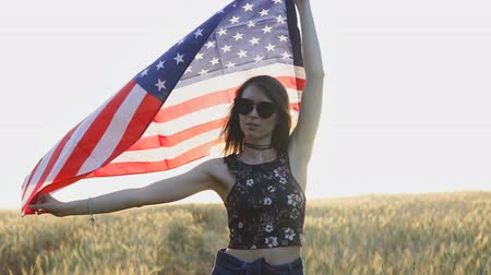 Young patriotic woman holding USA flag at sunset in slow motion. Independence Day concept Vídeos