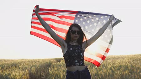 Young woman with national american flag outdoors at sunset. USA Independence Day concept. Slow motion