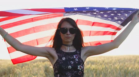 Portrait of pretty teen girl holding USA flag at sunset