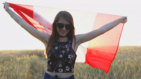 Young patriotic girl holding Canada flag at sunset in slow motion.