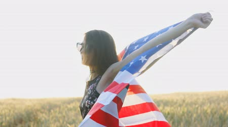 гражданство : Young patriotic girl with flag of the United States of America USA at sunset. Slow motion
