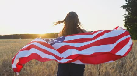 homeland : Young american girl running with flag of the United States of America at sunset. USA Independence Day concept