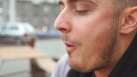 étkező : Close up of young man eating tasty burger in street food cafe Stock mozgókép