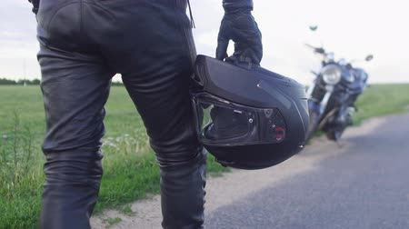 védősisak : Young man biker holding helmet equipment with leather jacket for safety protection when walking to motorcycle