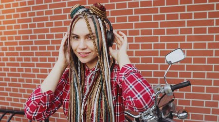 dread : Stylish girl with dreadlocks listens to music in headphones
