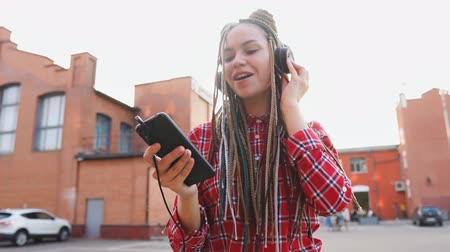 braid hairs : Trendy teenage girl with dreadlocks listening to music on headphones and using smartphone