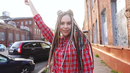 braids : Girl enjoying cool new hairstyle in the city. Portrait of joyful carefree woman with dreads
