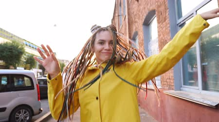 braid hairs : Portrait of carefree girl with dreadlocks jumping and dancing wearing yellow jacket