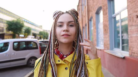 braid hairs : Portrait of smiling trendy teen girl with dreadlocks in urban background, slow motion Stock Footage