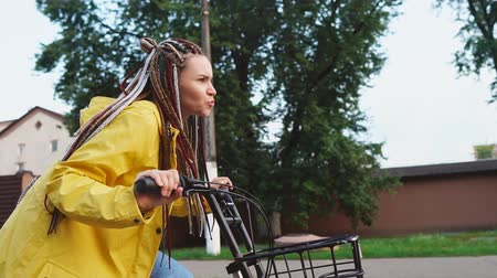 raszta : Young hipster girl with dreadlocks riding yellow vintage bicycle and having fun