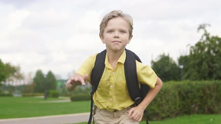 field study : Happy little boy with backpack running in park, slow motion. Back to school concept