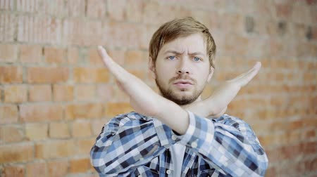 отказ : Portrait of Young Man showing stop sign, Dislike, Rejecting Gesture, Disagree Sign, Crossing hands