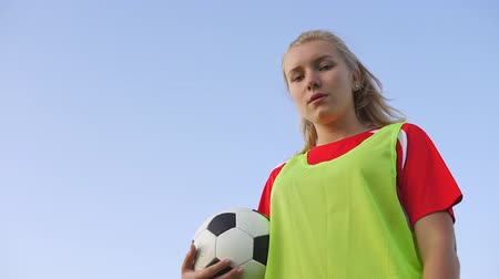 jarse : Bottom view portrait of a confident teen girl football player with a soccer ball