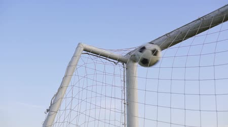 going round : Close-up of a soccer ball going into the back of the football net with a blue sky background Stock Footage