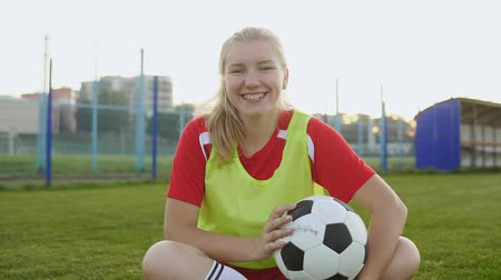 jarse : Portrait of a cute teenager girl football player sitting on field with soccer ball