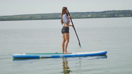 sucção : Young girl on stand up paddle board surfboard surfing in ocean sea Stock Footage