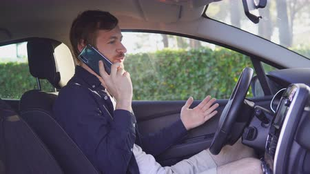 cars traffic : Handsome young man talking on his smart phone and smiling while sitting on the front seat