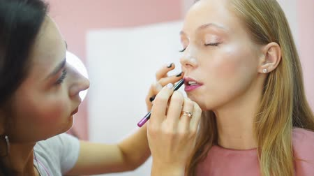 tusz do rzęs : Make up artist applying bright pink lipstick to lips of young model.