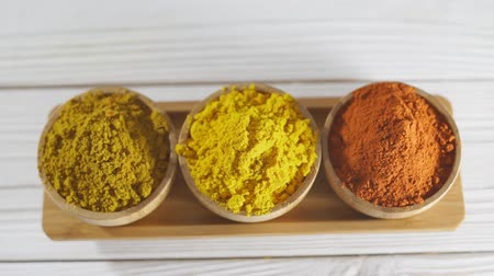 Three various spices in wooden bowls on white desk - turmeric, curry, paprika.