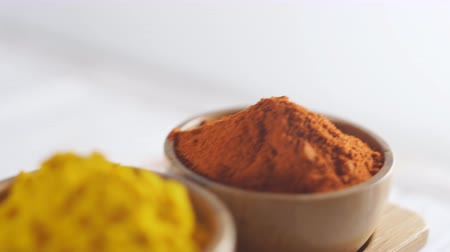 Various spices in wooden bowls on white surface - turmeric, curry, paprika. Stock Footage