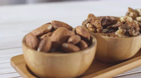 Assortment of three different kinds of raw nuts in small wooden bowls - walnut, almonds, cashews.