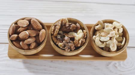 Top view of three various raw nuts in wooden bowls on white desk - walnut, almonds, cashews.