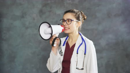 Portrait of woman doctor shouting loud into the megaphone