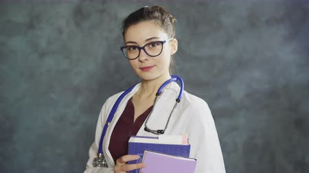 Portrait of woman doctor with stethoscope and books, looking at camera, smiling.