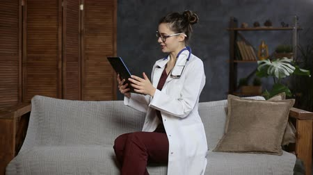 Woman doctor sitting on the couch and having a video call conference by tablet. Consulting patient online